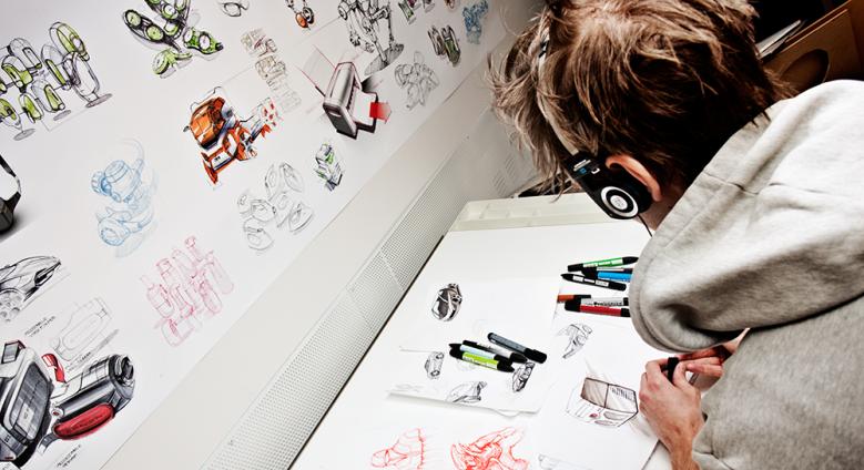 Product designer wearing headphones, sketching.